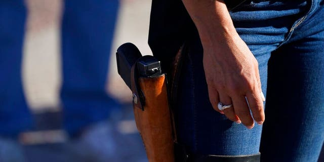 FILE - 이번 9 월. 4, 2020, 파일 사진, 로렌 보 버트, then-Republican candidate for the U.S. House of Representatives seat in Colorado's vast 3rd Congressional District, carries a gun during a freedom cruise staged by her supporters in Pueblo West, Colo. The district's newest representative, Boebert, is unabashed and social media-savvy. (AP 사진 / David Zal파일ski, File)