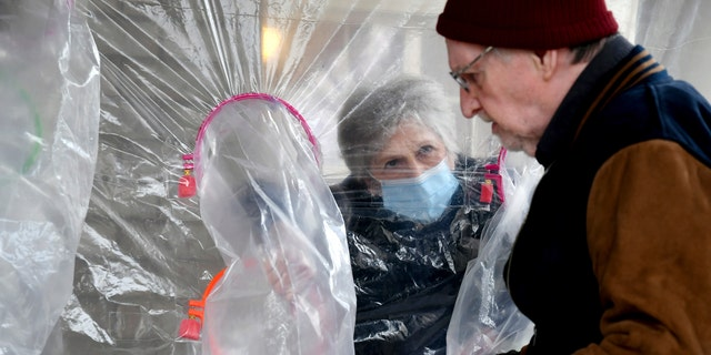 "Lynda Hartman, 75, visits her 77-year-old husband, Len Hartman, in a ""hug tent"" set up outside the Juniper Village assisted living center in Louisville, Colorado, on Wednesday. (AP Photo/Thomas Peipert)"