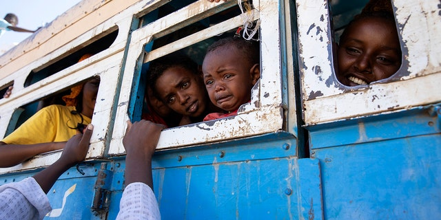Refugees fleeing the conflict in Ethiopia's Tigray region ride a bus going to the Village 8 temporary shelter, near the Sudan-Ethiopia border, in Hamdayet, eastern Sudan, Dec. 1, 2020. (Associated Press)