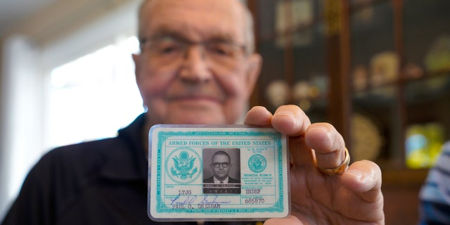 Paul Grisham holds his 1968 Navy ID card, which was found inside his wallet. (Nelvin C. Cepeda/The San Diego Union-Tribune via AP)