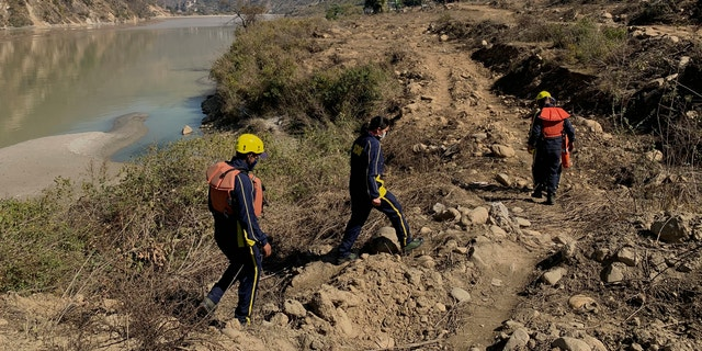 Rescuers arrive to search for bodies in the downstream of Alaknanda River in Rudraprayag, northern state of Uttarakhand, India, Monday, Feb.8, 2021. More than 2,000 members of the military, paramilitary groups and police have been taking part in search-and-rescue operations after part of a Himalayan glacier broke off Sunday and sent a wall of water and debris rushing down the mountain. (AP Photo/Rishabh R. Jain)