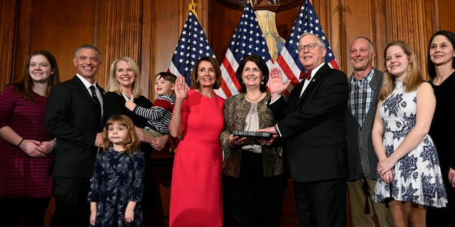 FILE - In this Jan. 3, 2019 file photo, House Speaker Nancy Pelosi of Calif., poses during a ceremonial swearing-in with Rep. Ron Wright, R-Texas, fourth from right, on Capitol Hill in Washington during the opening session of the 116th Congress. Wright, the Texas Republican who had battled health challenges over the past year including lung cancer treatment died Sunday, Feb. 7, 2021, more than two weeks after contracting COVID-19, his office said Monday, Feb. 8. He was 67. (AP Photo/Susan Walsh, File)