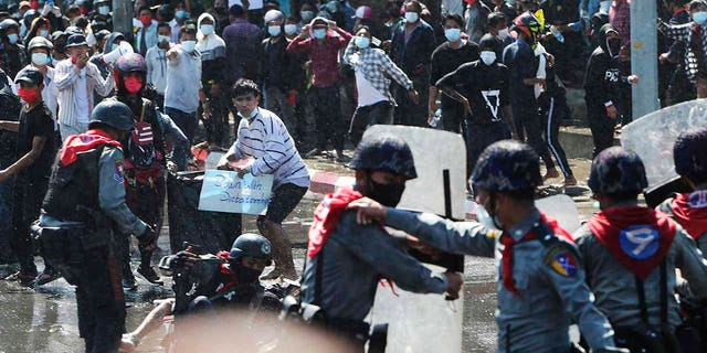 Protesters run after police fire warning-shots and use water cannons to disperse them during a protest in Mandalay, Burma on Tuesday, Feb. 9, 2021. Police cracked down Tuesday on the demonstrators protesting against Burma's military takeover who took to the streets in defiance of new protest bans. (AP Photo)