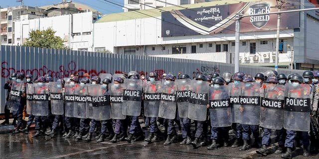 Police in riot gear march to take a position to block demonstrators at an intersection during a protest in Mandalay, Burma, Tuesday, Feb. 9, 2021. Police were cracking down on the demonstrators against Burma's military takeover who took to the streets in defiance of new protest bans. (AP Photo)