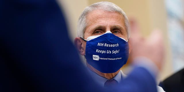 Dr. Anthony Fauci, director of the National Institute of Allergy and Infectious Diseases, listens as President Joe Biden speaks during a visit at the Viral Pathogenesis Laboratory at the National Institutes of Health (NIH), Thursday, Feb. 11, 2021, in Bethesda, Md. (AP Photo/Evan Vucci)