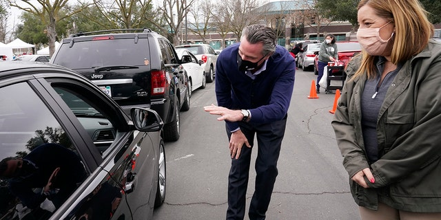 Gov. Gavin Newsom leans over to talk with a person waiting to get a COVID-19 vaccination at a drive-thru vaccination center at Natomas High School in Sacramento, Calif., Thursday, Feb. 11, 2021. Appointments were needed for the 1,000 vaccinations to be administered for those 65 and over, first responders, health workers, teachers, food and agricultural employers. Called an equitable distribution site, it prioritized those disproportionally impacted by COVID-19, was collaboration between the Natomas' Unified School District, Sacramento County Public Health Department and Sacramento Vice Mayor Angelique Ashby, behind Newsom, who represents the area. (AP Photo/Rich Pedroncelli)