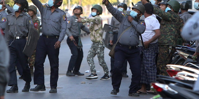 A policeman aims a slingshot towards an unknown target during a crackdown on anti-coup protesters holding a rally in front of the Myanmar Economic Bank in Mandalay, Burma on Monday, Feb. 15, 2021. (AP Photo)