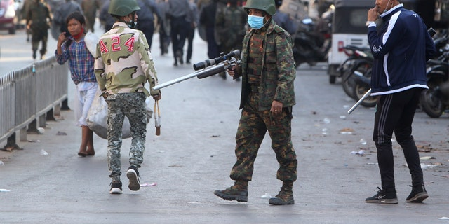 A soldier holds a long firearm during a crackdown on anti-coup protesters holding a rally in front of the Myanmar Economic Bank in Mandalay, Burma on Monday, Feb. 15, 2021.  (AP Photo)