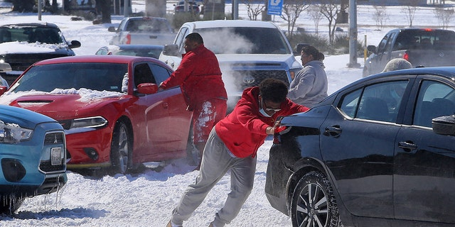 People push a car free after spinning out in the snow Monday, Feb. 15, 2021 in Waco, Texas. (Associated Press)