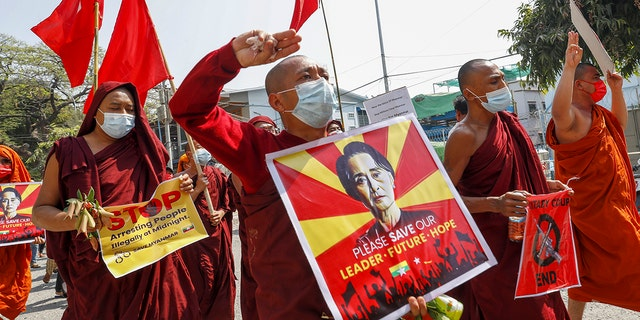 Buddhist monks and nuns display pictures of detained Burma leader Aung San Suu Kyi during a protest against the military coup in Mandalay, Myanmar on Tuesday, Feb. 16, 2021. (AP Photo)