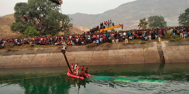 Rescuers work at the site of a bus accident in Sidhi district, in the central Indian state of Madhya Pradesh, Tuesday, Feb. 16, 2021. (Madhya Pradesh District Public Relation Office Sidhi via AP)
