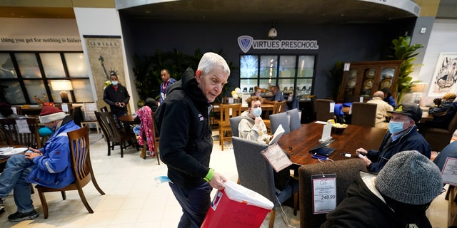 Owner Jim McIngvale collects trash inside his Gallery Furniture store, which opened as a shelter Wednesday, Feb. 17, 2021, in Houston. Millions in Texas still had no power after a historic snowfall and single-digit temperatures created a surge of demand for electricity to warm up homes unaccustomed to such extreme lows, buckling the state's power grid and causing widespread blackouts. (AP Photo/David J. Phillip)