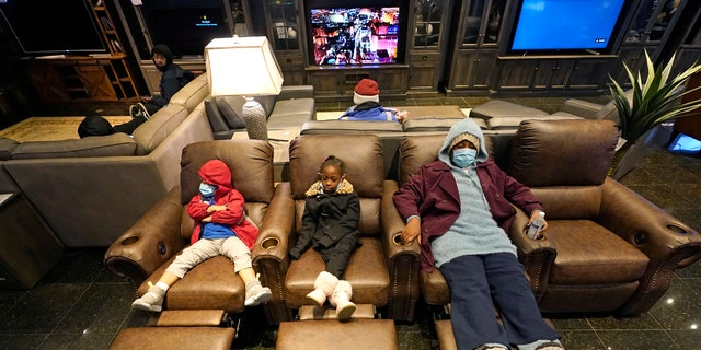 Joecyah Heath, sinistra, Morning Day, centro, and Jenesis Heath rest in recliners at a Gallery Furniture store, which opened as a shelter Wednesday, Feb. 17, 2021, a Houston. Millions in Texas still had no power after a historic snowfall and single-digit temperatures created a surge of demand for electricity to warm up homes unaccustomed to such extreme lows, buckling the state's power grid and causing widespread blackouts. (AP Photo/David J. Phillip)