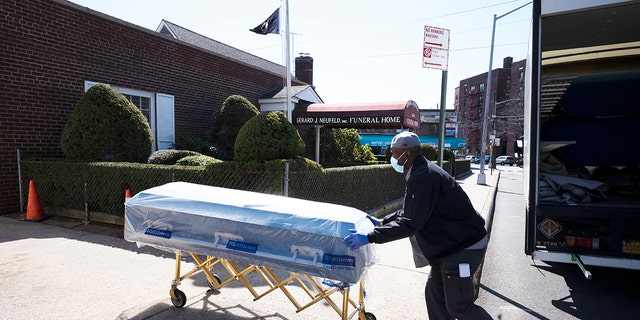 William Samuels delivers caskets to the Gerard Neufeld Funeral Home during the coronavirus pandemic in the Queens borough of New York on March 27, 2020.  (AP Photo/Mark Lennihan)