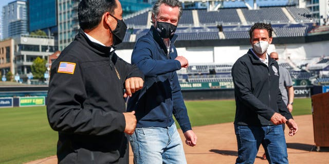 FILE: California Governor Gavin Newsom, center, bumps elbows with San Diego Mayor Todd Gloria after a news conference at Petco Park, which will host a vaccination site in a parking lot next to the ballpark in San Diego.