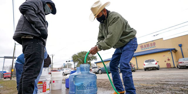 Leovardo Perez, right, fills a water jug using a hose from a public park water spigot Thursday, Feb. 18, 2021, in Houston. (Associated Press)