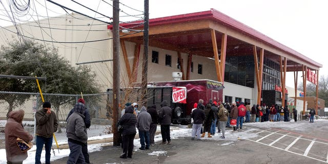 People stand in line outside an HEB grocery store in the snow Thursday, Feb. 18, 2021, in Austin, Texas. (Associated Press)