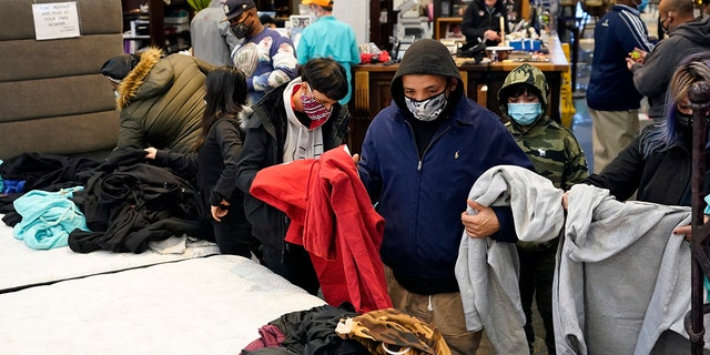 People select shirts and sweatshirts being given away at a Gallery Furniture store after the owner opened his business as a shelter for those without power at their homes in Houston, Feb. 16, 2021. ​​​​​​(Associated Press)