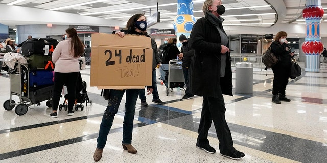 Mary Kay Hoffman, left, and Cindy Durham, right, wait for the arrival of Sen. Ted Cruz, R-Texas, at the international arrivals terminal at George Bush Intercontinental Airport Thursday, Feb. 18, 2021, in Houston. (AP Photo/David J. Phillip)
