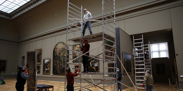 Workers at the Louvre museum set up scaffolding in the museum. (AP Photo/Thibault Camus)