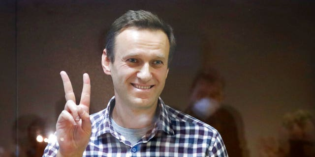 Russian opposition leader Alexei Navalny gestures as he stands in a cage in the Babuskinsky District Court in Moscow, Russia, Saturday, Feb. 20, 2021. (AP Photo/Alexander Zemlianichenko)
