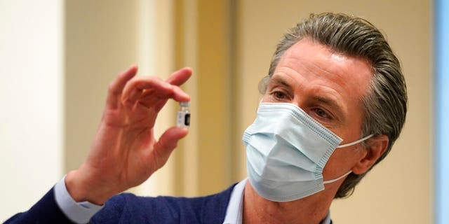 FILE: California Gov. Gavin Newsom holds up a vial of the Pfizer-BioNTech COVID-19 vaccine at Kaiser Permanente Los Angeles Medical Center in Los Angeles.