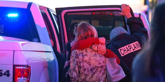 A Jefferson Parish Sheriff's Office Chaplain stands next to two women hugging at the scene of a multiple fatality shooting at the Jefferson Gun Outlet in Metairie, La. Saturday, Feb. 20, 2021. (Associated Press)