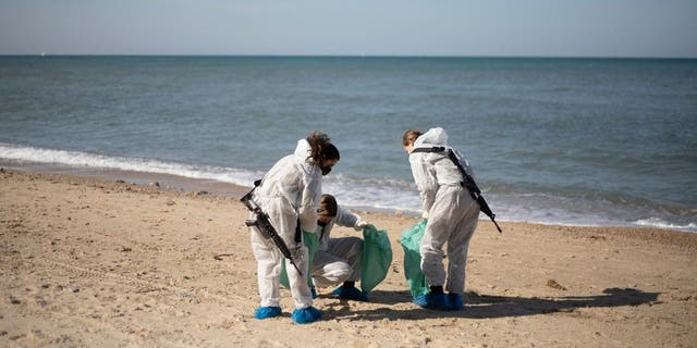 On Monday, February 22, 2021, in the Sharon Beach Nature Reserve near Gaza, Israel, Israeli soldiers in protective clothing wash tar from the beach after an oil spill in the Mediterranean Sea (AP Photo / Ariel Schalit)