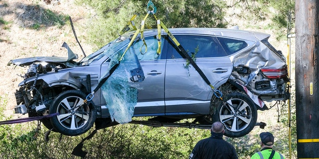 A crane is used to lift a vehicle following a rollover accident involving golfer Tiger Woods, Tuesday, Feb. 23, 2021, in the Rancho Palos Verdes suburb of Los Angeles. (AP Photo/Ringo H.W. Chiu)
