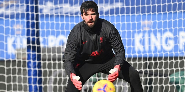 Liverpool's goalkeeper Alisson warms up ahead of the English Premier League soccer match between Leicester City and Liverpool at the King Power Stadium in Leicester, England, Saturday, Feb. 13, 2021. (Michael Regan/Pool Photo via AP)