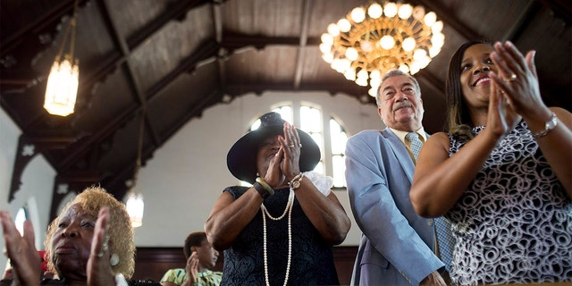 FILE - In this Sunday, July 10, 2016 file photo, parishioners clap during a worship service at the First Baptist Church, a predominantly African-American congregation, in Macon, Ga. (AP Photo/Branden Camp)