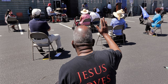 FILE - In this Sunday, July 19, 2020 file photo, church parishioners sit apart socially distanced at a prayer vigil for racial justice at Immaculate Conception Catholic Church in Seattle. (AP Photo/Elaine Thompson)