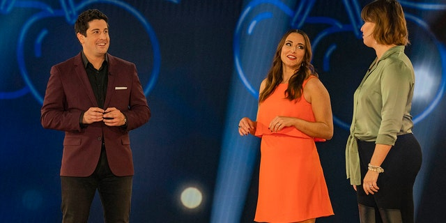 """L-R: Host Jason Biggs with contestants Cara and Gwen in an episode of """"Cherries Wild.'"""