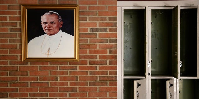 A portrait of St. John Paul II hangs beside a row of empty lockers in the main hallway of Quigley Catholic High School in Baden, Pa., in June 2020. (AP)