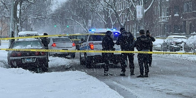 Officers investigate a shooting in Chicago last month despite heavy snowfall impacting the city.