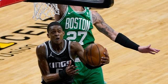 Sacramento Kings guard De'Aaron Fox, left, goes to the basket against Boston Celtics center Daniel Theis during the first quarter of an NBA basketball game in Sacramento, Calif., Wednesday, Feb. 3, 2021. (AP Photo/Rich Pedroncelli)