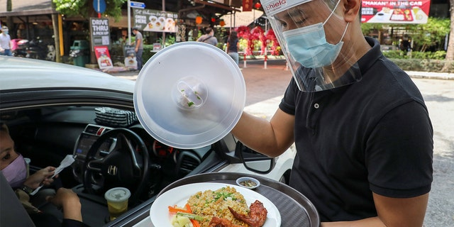 A waiter serves a customer outside Padi House restaurant for 'dine in car' service. (REUTERS/Lim Huey Teng)