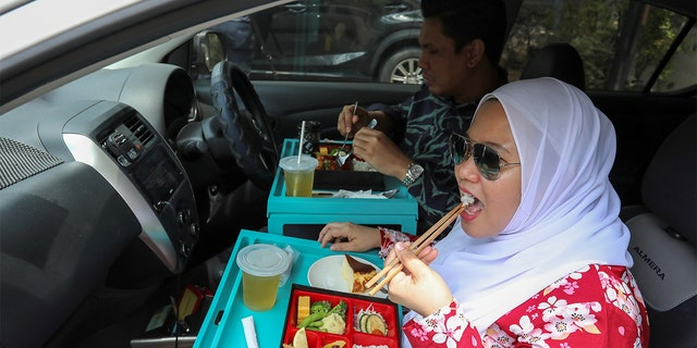 Customers dine in their car outside Padi House restaurant, during a lockdown due to the coronavirus, in Cyberjaya, Malaysia. (REUTERS/Lim Huey Teng)