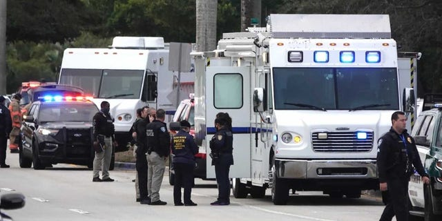 Law enforcement gathers near the scene of a shooting that wounded several FBI agents in Sunrise, Fla., Tuesday, Feb. 2, 2021. (Joe Cavaretta/South Florida Sun-Sentinel via AP)