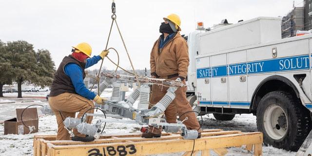Workers repair a power line in Austin, Texas, on Feb. 18, 2021. (Thomas Ryan Allison/Bloomberg via Getty Images)