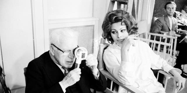 Charlie Chaplin looking a film negative through a magnifying glass while sitting close to actress Sophia Loren during filming on the set of the movie 'A Countess from Hong Kong' at the Pinewood Studios in London, 1966