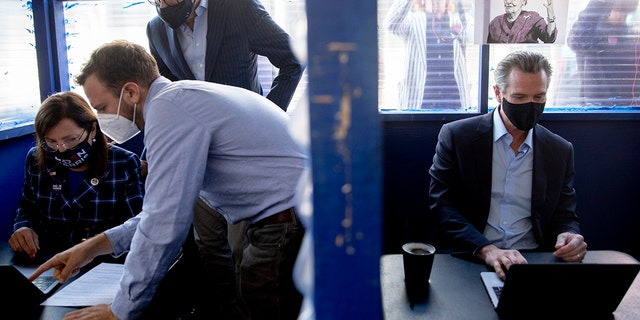 SAN FRANCISCO, CA - NOV. 3: Lieutenant Governor Eleni Kounalakis (left) and Governor Gavin Newsom sit in nearby booths outside of Manny's cafe and communal space in San Francisco, Calif. Tuesday, November 3, 2020 to phone bank for democratic candidates. (Jessica Christian/The San Francisco Chronicle via Getty Images)