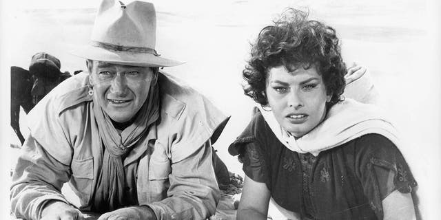 John Wayne and Sophia Loren laying in the sand in a scene from the film 'Legend Of The Lost', 1957.