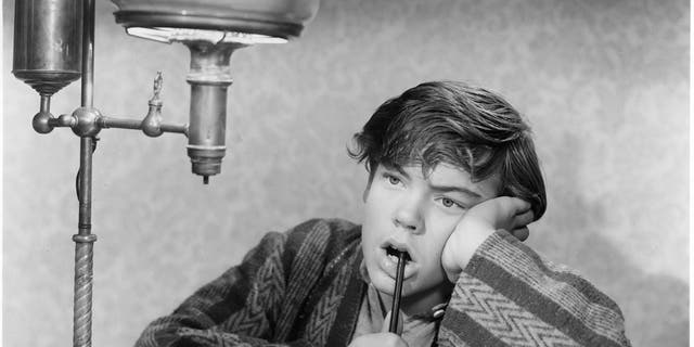Bobby Driscoll with pen in mouth in a scene from the film 'When I Grow Up', 1951.
