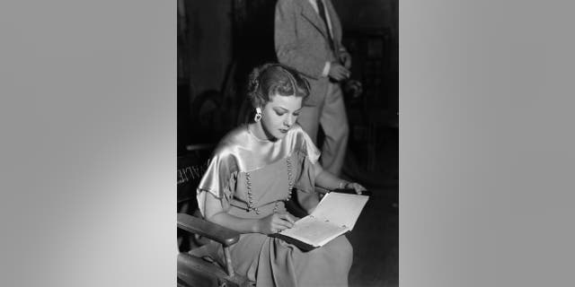 Actress Elissa Landi concentrates on a bit of writing between takes of the Paramount film 'The Great Flirtation', directed by Ralph Murphy.