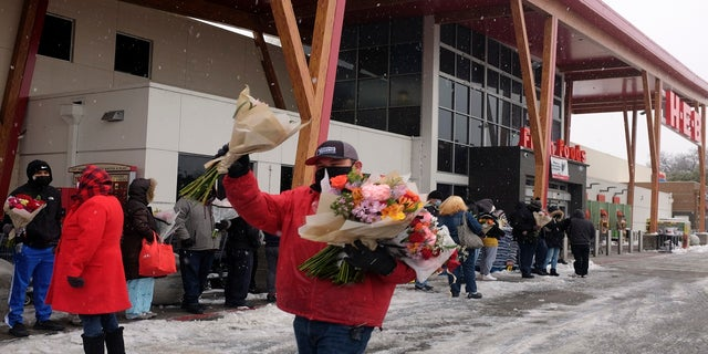 An HEB grocery store employee hands out flowers to customers waiting in line in the snow Thursday in Austin, Texas. (AP)