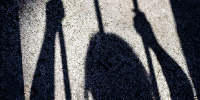 Shadow of a prisoner inside a prison cell projected on the ground.