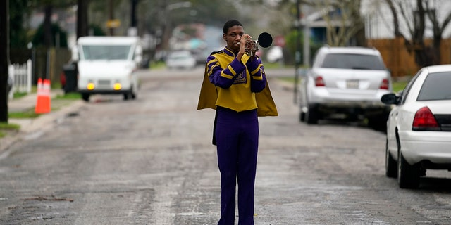 Elvin King III, a senior at Warren Easton High and member of their marching band which was slated to perform in a now-canceled parade, poses for a portrait in front of his home in New Orleans. (AP Photo/Gerald Herbert)