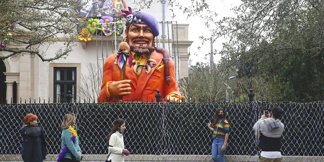 Passersby stop for photos in front of a house decorated for Mardi Gras.