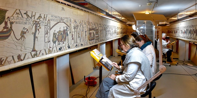 This photo provided by Bayeux townhall shows technicians working at the tapestry in Bayeux, Normandy on Jan. 8 2020. (Ville de Bayeux via AP)